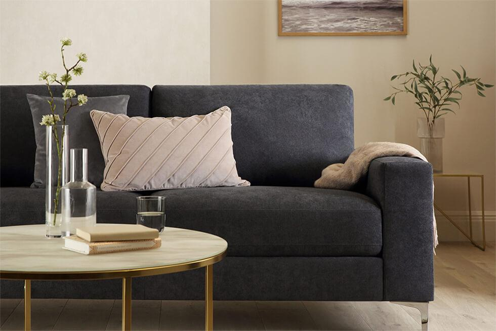 Neutral living room with dark grey fabric sofa with chrome legs and a round coffee table