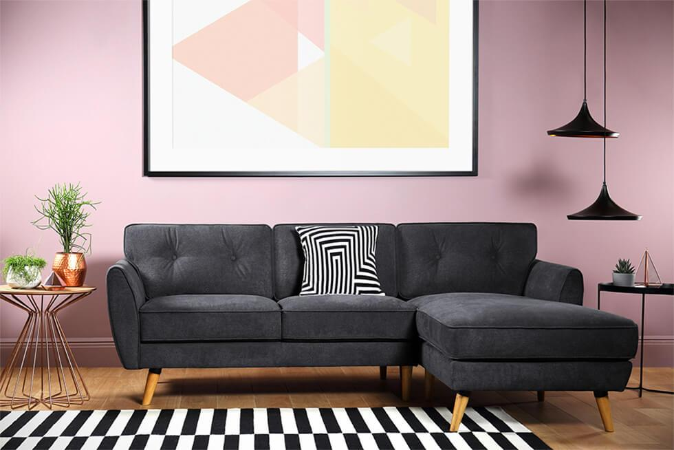 Statement pink living room with mid-century fabric sofa, monochrome rug and pendant lamps