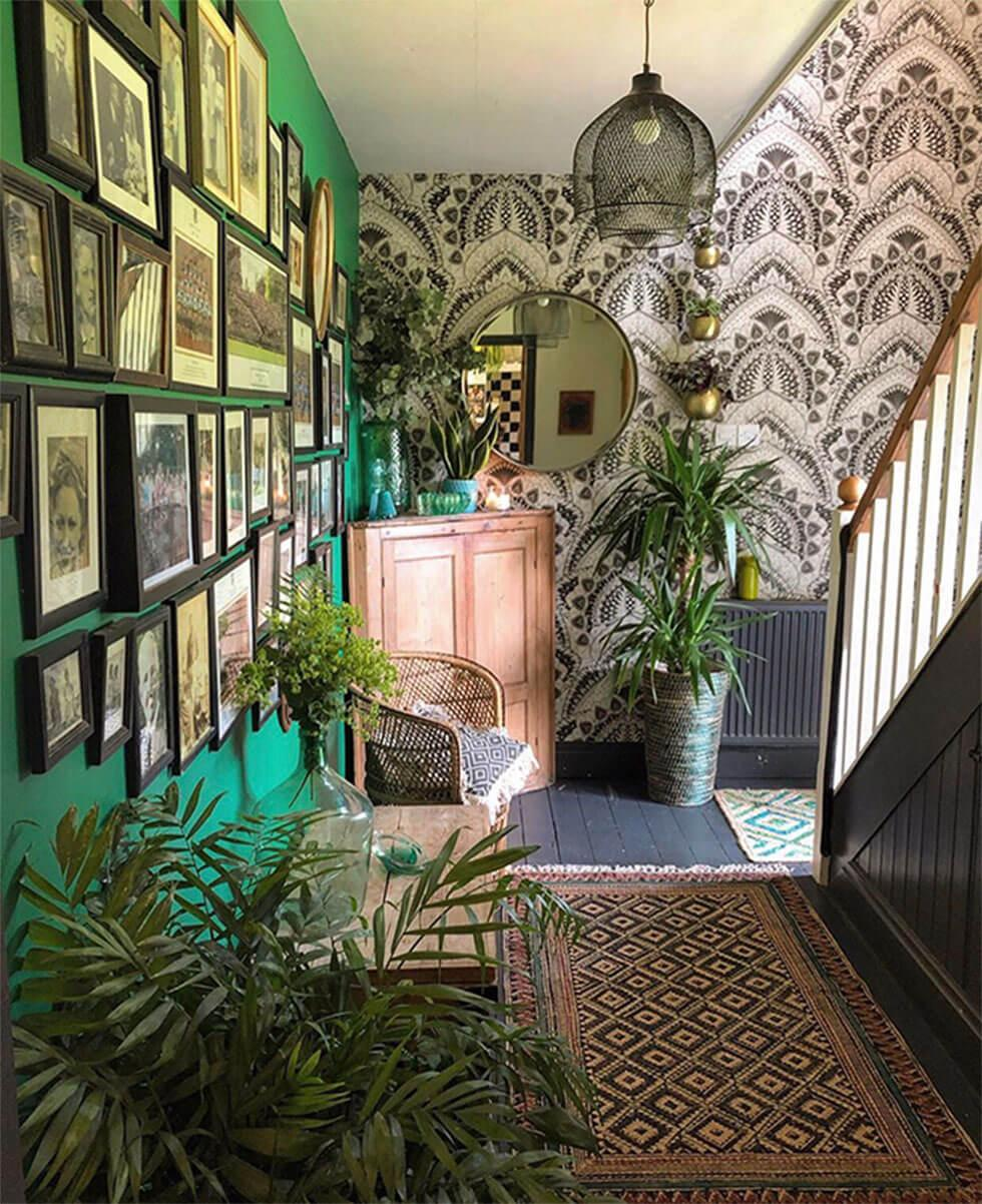 Green feature photo wall in the hallway with contrasting wallpaper
