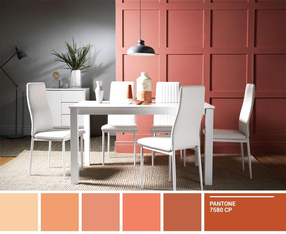 A white dining set against a terracotta and grey wall.