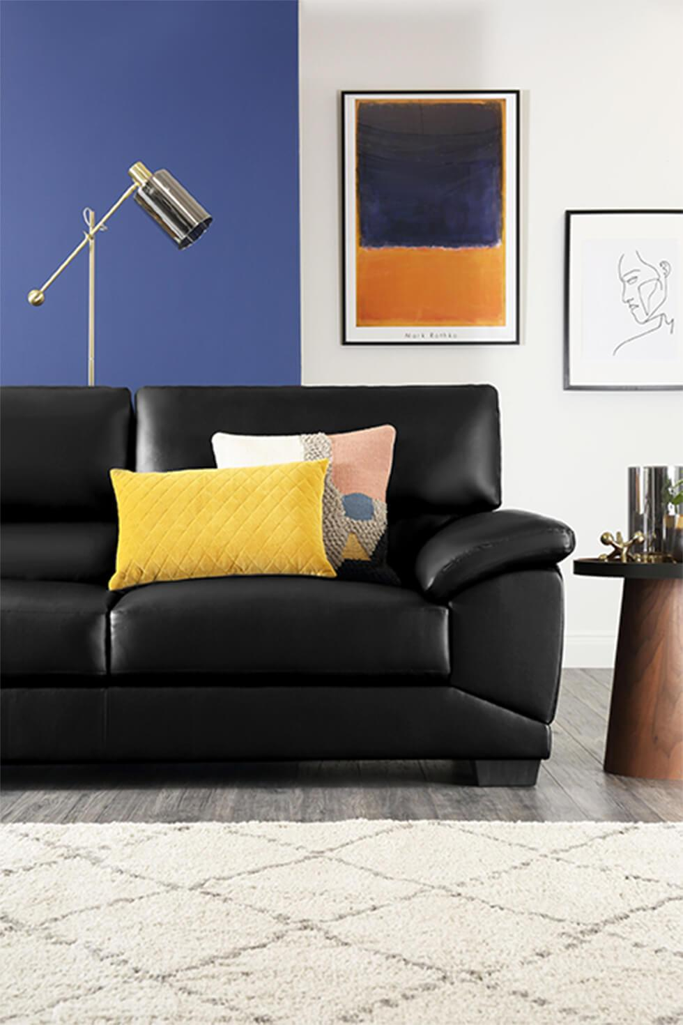 Black leather sofa with colourblock blue feature wall and framed art