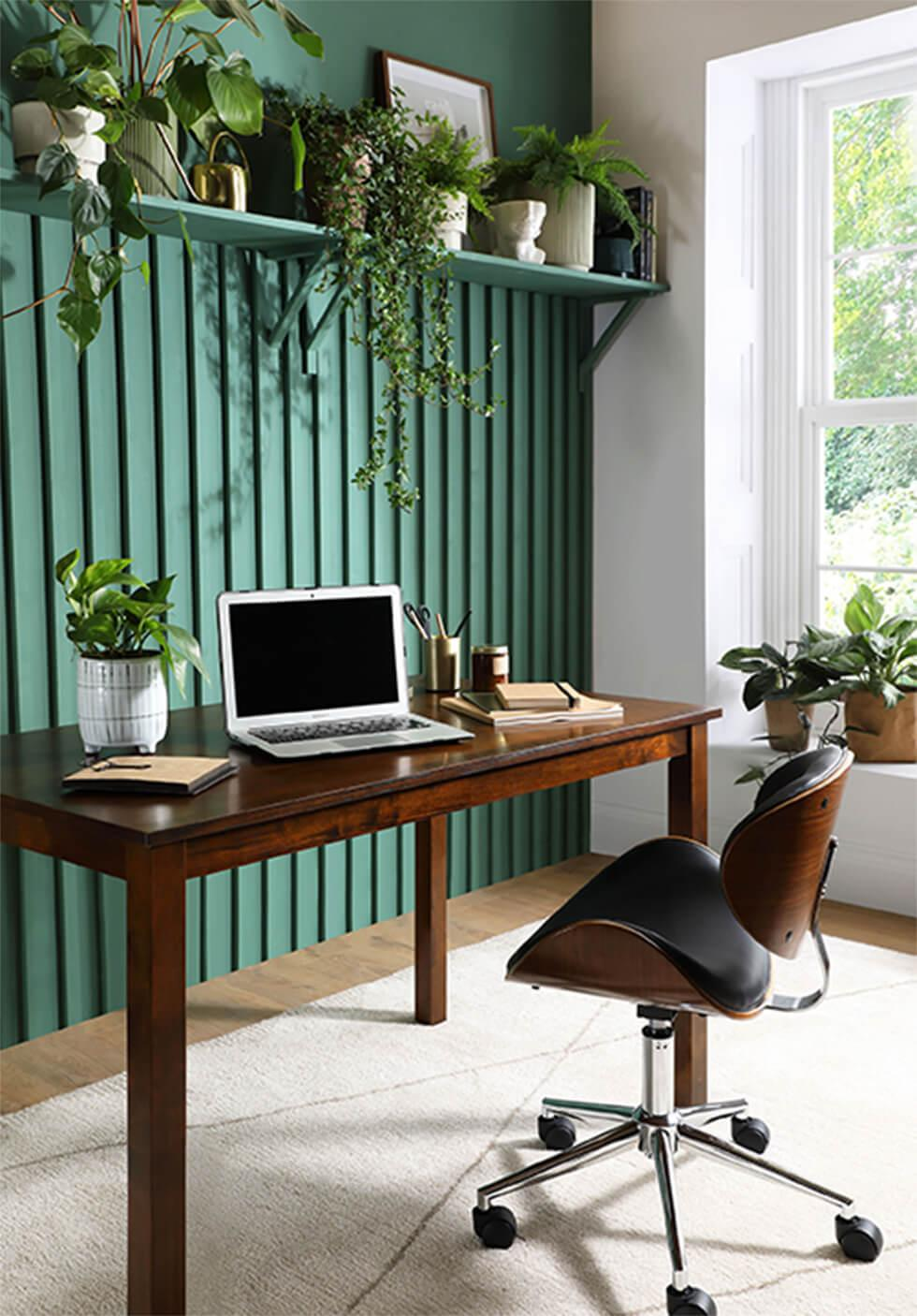 Home office with feature green shiplap wall, indoor plants and dark wood dining table