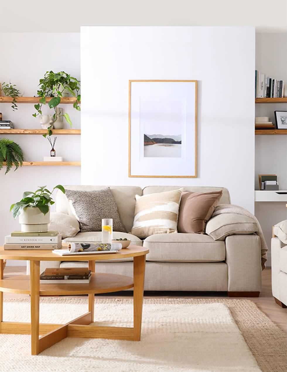 Light neutral living room with linen sofa and round wooden coffee table