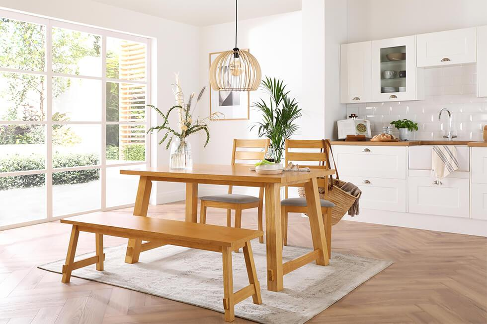 Neutral white dining room with wooden dining table and bench with indoor plants and statement lamp