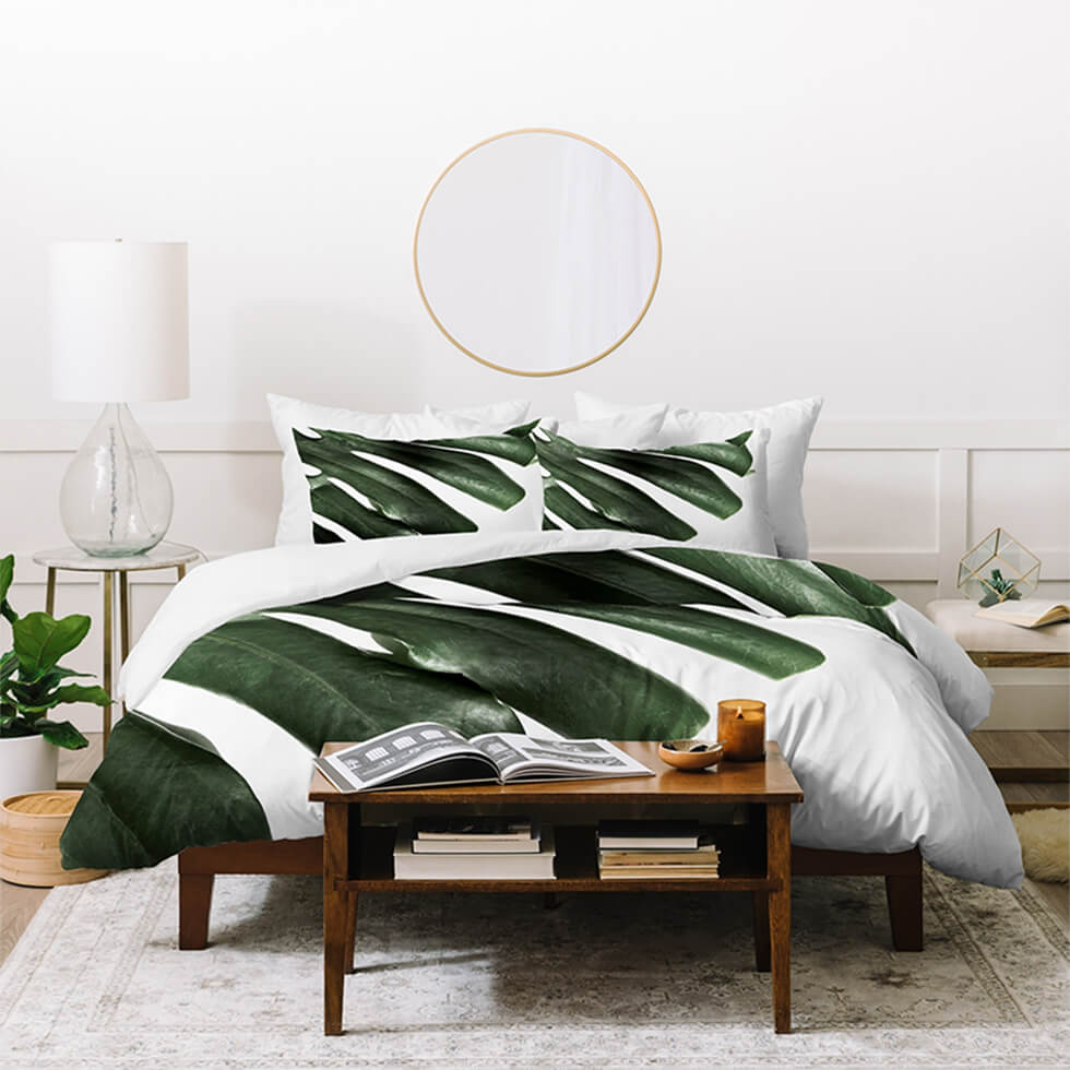 White scandinavian bedroom with tropical print bedsheets