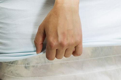 Hand switching the covers on a mattress.