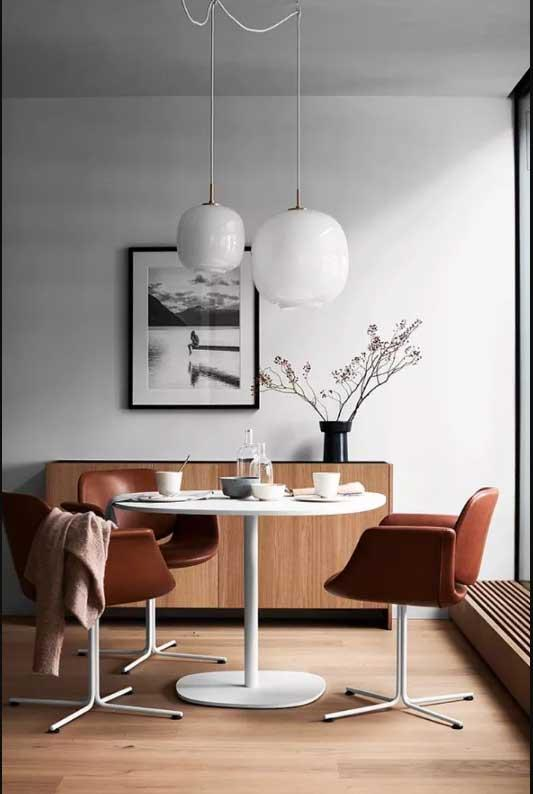Dining room with white walls, wooden flooring and white table with leather swan chairs.
