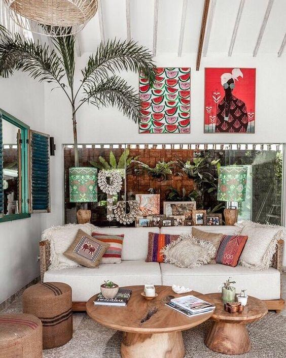 Balinese living room with wooden furniture, ikat cushions and colourful artwork.